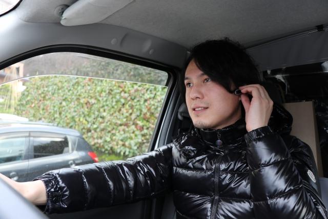 車でハンズフリー通話する男性